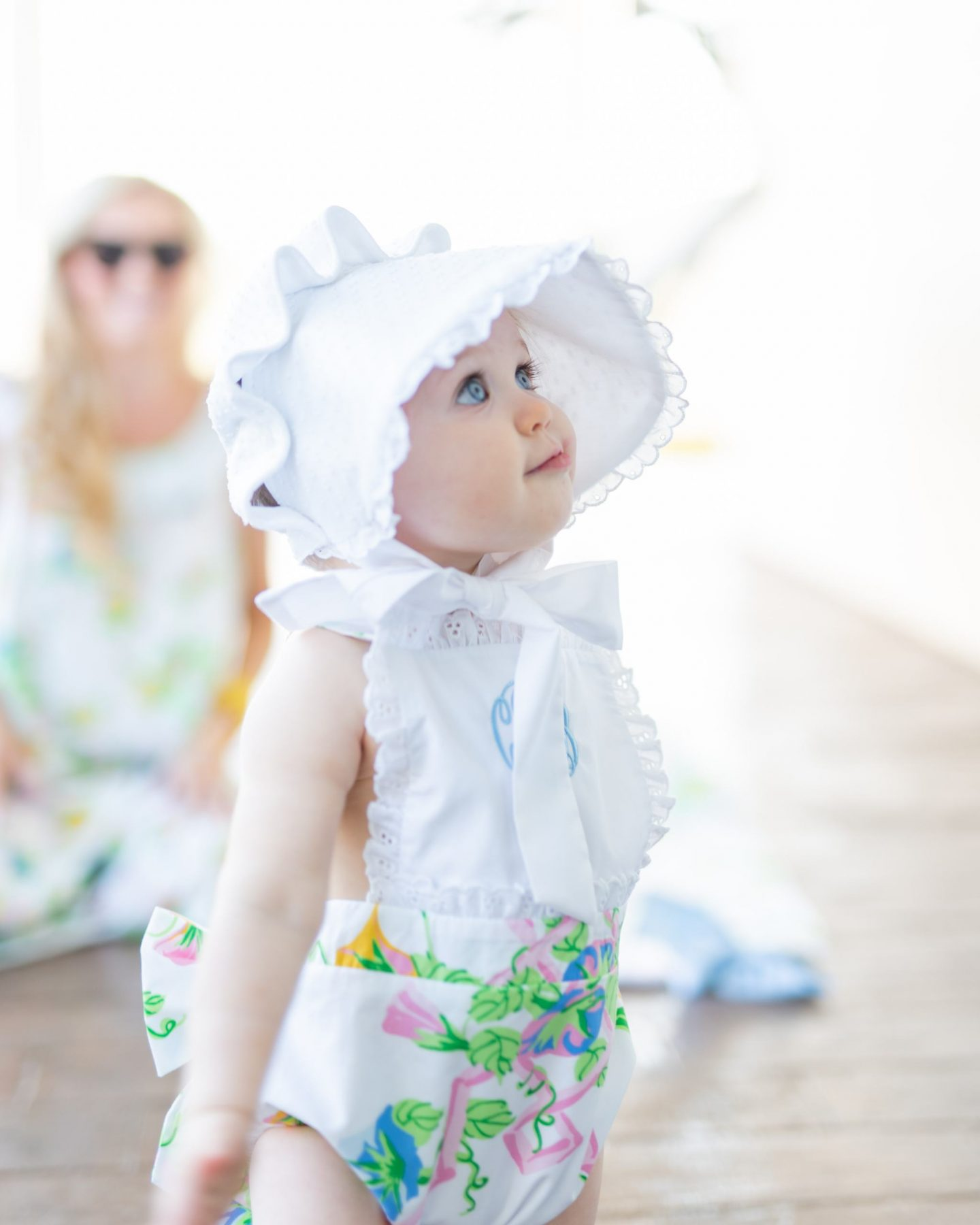 baby girl with sunsuit and bonnet in a floral print