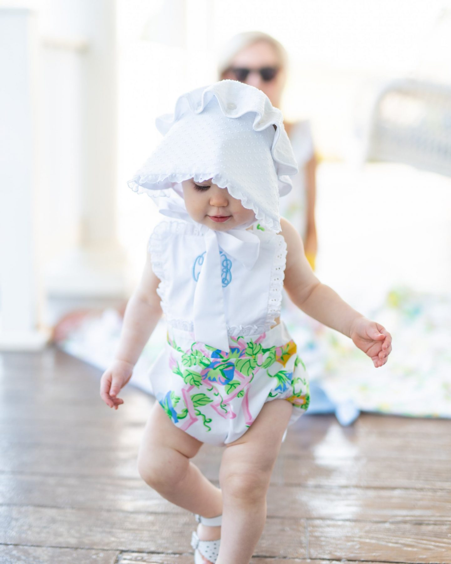 baby girl in a floral sunsuit and white bonnet playing on the porch in the sunlight