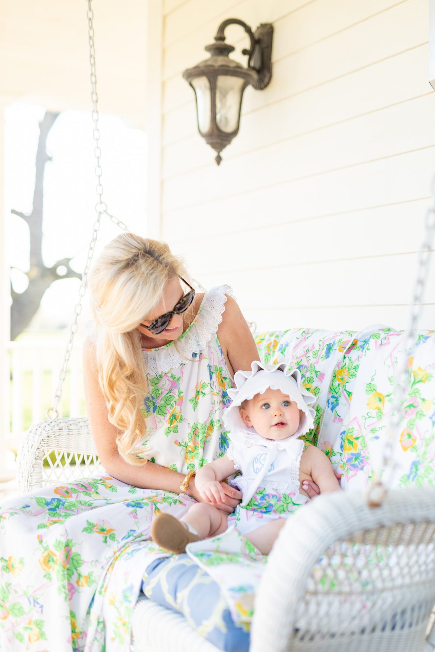 mom with blonde hair and daughter in a sunset and bonnet sitting on swing on a white front porch