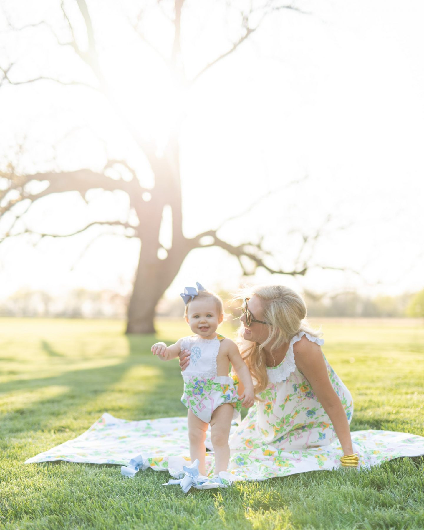 mommy and daughter fashion sitting with a picnic under a southern sky in matching outfits