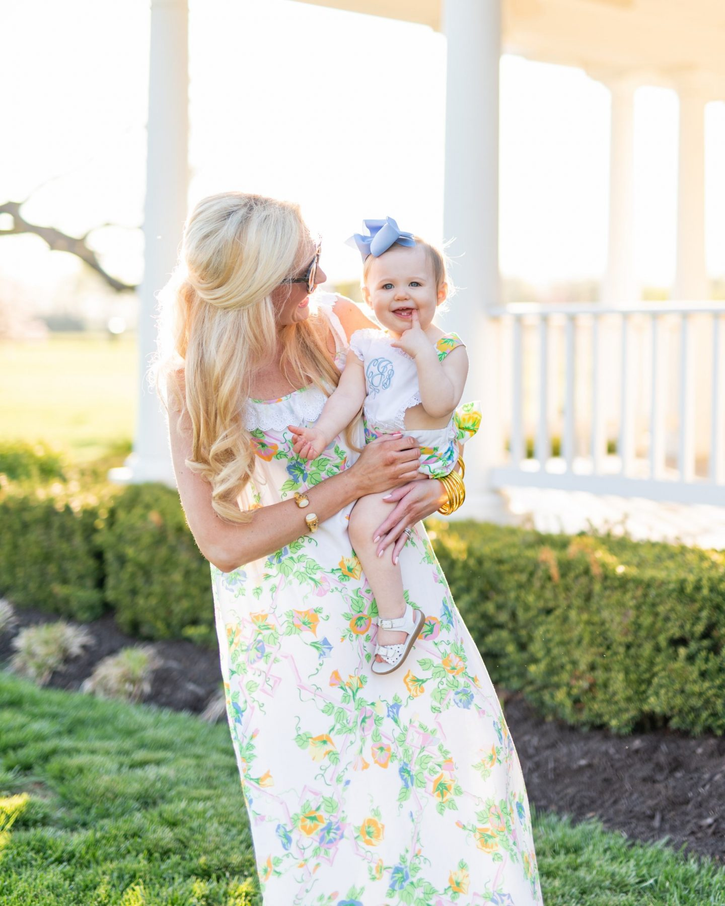 blonde mom with tortoise sunglasses and a floral maxi holding a baby girl with a sunsuit and blue bow